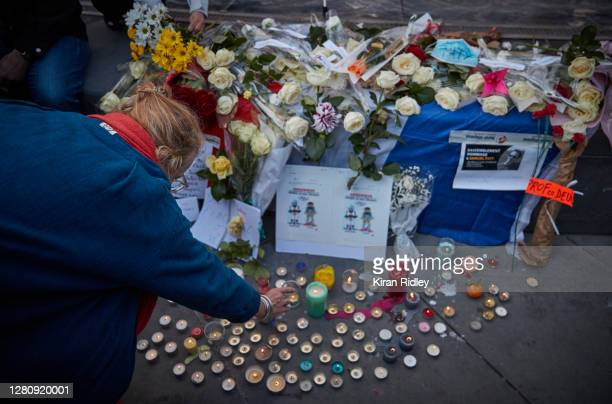 Woman lights a candle for the murdered school teacher Samuel Paty during an anti-terrorism vigil at Place de La Republique on October 18, 2020 in...