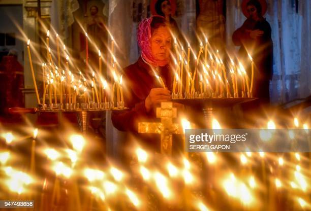 A woman lights a candle in a church during Radunitsa day the Russian Orthodox Church commemoration of the departed on April 17 2018 in the village of...