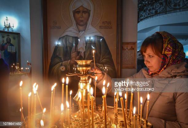 TOPSHOT A woman lights a candle in a church in Bishkek on January 7 2019 Orthodox Christians celebrate Christmas on January 7 in the Middle East...