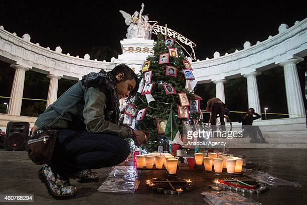 A woman lights a candle in front of a Christmas tree decorated with pictures of 43 missing students from the Isidro Burgos rural teachers college in...