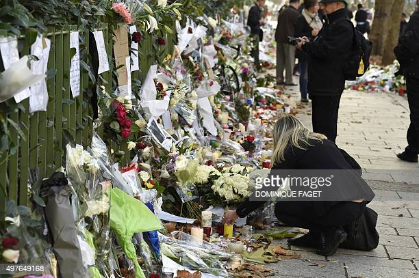 A woman lights a candle in front of a makeshift memorial for the victims of the attacks near the Bataclan theatre in Paris on November 18 2015 Three...