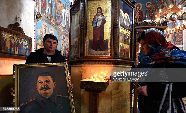 A woman lights a candle in front of a portrait of late Soviet dictator Joseph Stalin at a church in Stalin's native town of Gori some 80 kms outside...