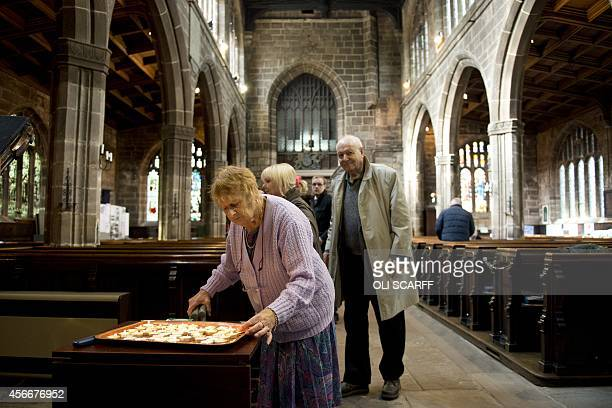 A woman lights a candle in memory of murdered aid worker Alan Henning in Eccles Parish Church in Eccles north west England on October 5 2014 Britain...