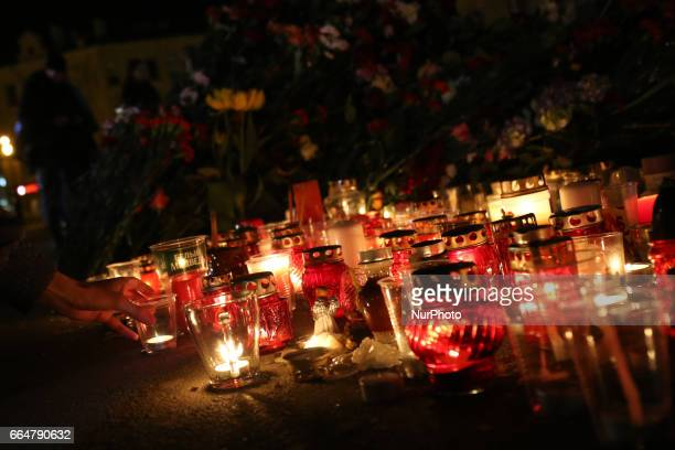 A woman lights a candle in memory of the victims of the St Petersburg Metro explosion at an entrance to Spasskaya Metro Station in St Petersburg on...