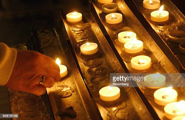 A woman lights a candle in Westminster cathedral in London Saturday April 2 2005 Pope John Paul II's health has worsened with his breathing...