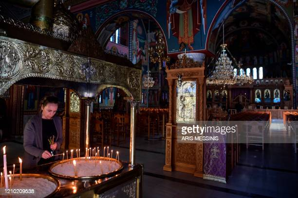 A woman lights a candle inside an empty Orthodox church during the Holy Friday celebrations on April 17 in Athens Easter is Greece's foremost...