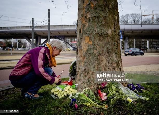 A woman lights a candle near the scene of the fatal shooting at 24 Oktoberplein in Utrecht The Netherlands 19 March 2019 the day after three people...