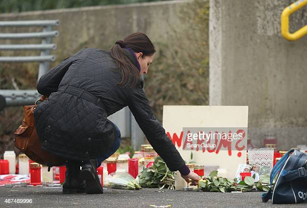 A woman lights a candle next to a sign that reads Why at the JosephKoenigGymnasium high school where pupils had come to pay tribute to 16 students...