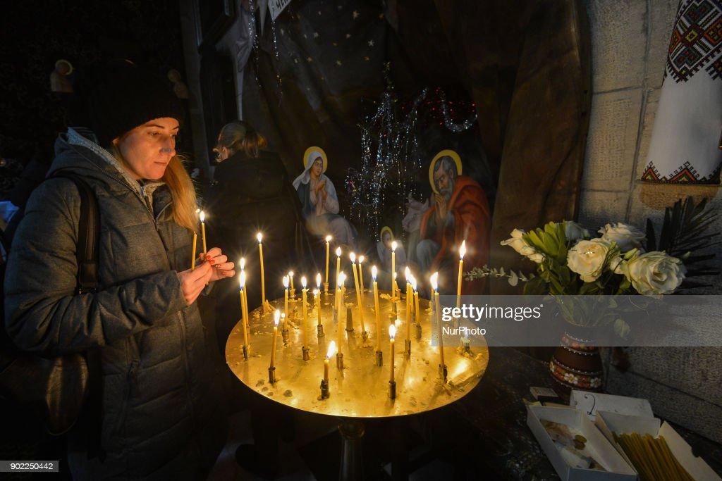 Eastern Orthodox Christmas.A Woman Lights A Candle On Eastern Orthodox Christmas Day