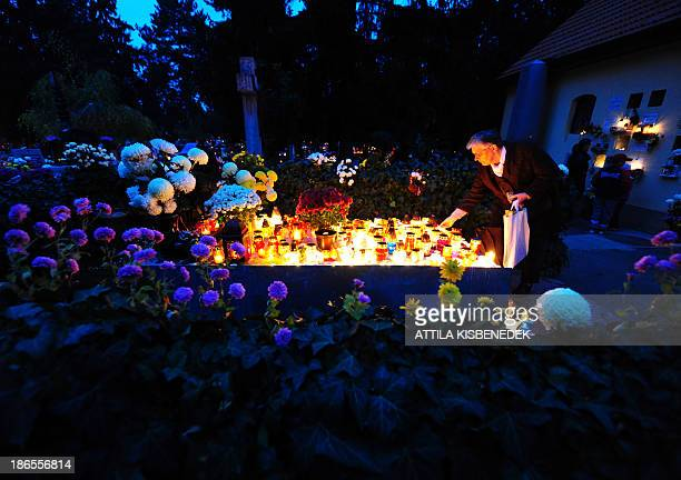 A woman lights a candle on the occasion of All Saints' Day on a tomb on the Hatvan street cemetery in Eger Hungary on November 1 2013 In Hungary...