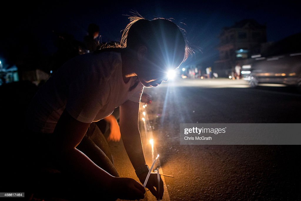 TACLOBAN, LEYTE, PHILIPPINES - NOVEMBER 08: A woman lights a candle on the roadside in San Jose during the candlelight memorial on November 8, 2014 in Tacloban, Leyte, Philippines. People lined the roads with candles all across Tacloban from the airport to downtown in remembrance of the victims of Typhoon Haiyan. Residents and typhoon survivors from across the central Philippines attended memorial services, candlelight vigils and visited mass graves honouring those who lost their lives one year ago when Typhoon Haiyan, the strongest typhoon ever to make landfall swept across the region, leaving more than 6000 dead and many more homeless.