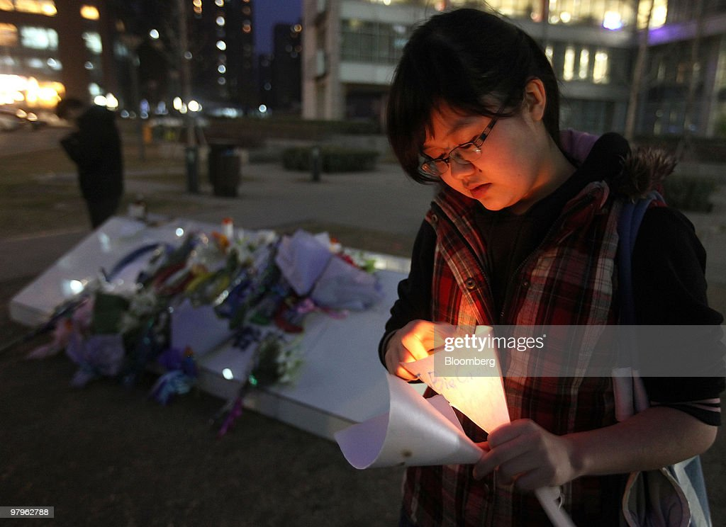 A woman lights a candle outside the Google Inc. offices in Beijing, China, on Tuesday, March 23, 2010. Google Inc., following through on a pledge to stop censoring search results in China, began serving mainland Chinese users via its unfiltered Hong Kong site, a move that could prompt the government to block the service. Photographer: Doug Kanter/Bloomberg via Getty Images