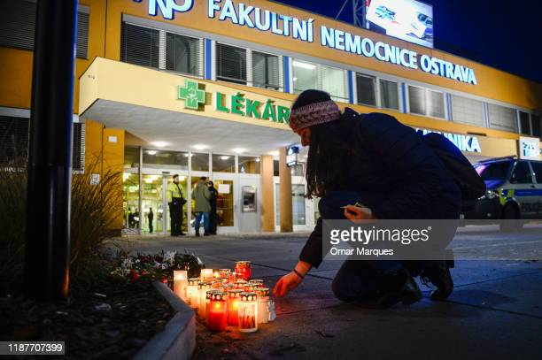 Woman lights a candle outside the Ostrava Teaching Hospital after a shooting incident on December 10, 2019 in Ostrava, Czech Republic. A gunman...