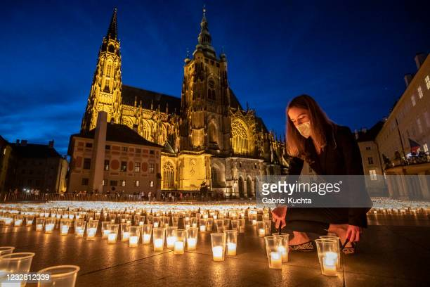 Woman lights a candle to commemorate victims of the COVD-19 pandemic at the Prague Castle on May 10, 2021 in Prague, Czech Republic. People...