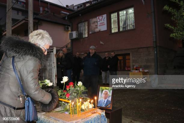A woman lights a candle where Kosovo Serb politician Oliver Ivanovic was killed in northern town of Mitrovica Kosovo on January 16 2018 Kosovo Serb...