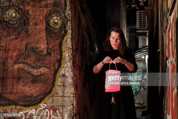 TOPSHOT A woman lights a candle with a Holy Fire from small candles left on a path outside the Metochion of the Holy Sepulchre in Athens where the...