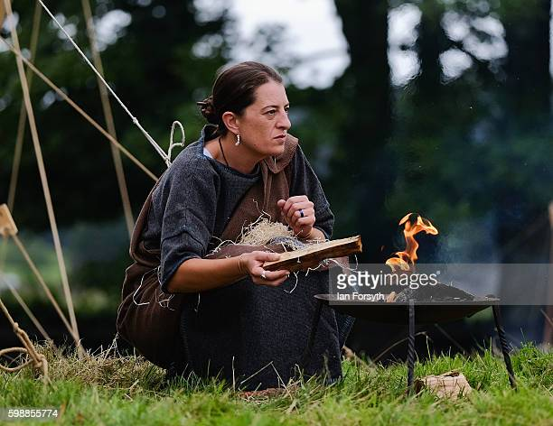 A woman lights a fire outside her tent as the lives of Roman Legionnaires are reenacted during the Hadrian's Wall Live event at Birdoswald Roman fort...