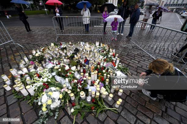 A woman lights a memorial candle at the Turku Market Square for the victims of a stabbing spree on August 19 2017 in Turku Police are now...