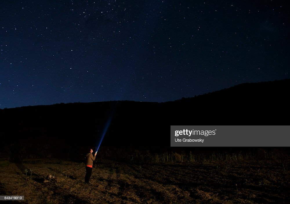 Woman with her torch under the Milky Way in the Andes : News Photo