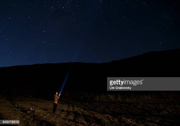 A woman lights a torch in the night sky over the Andes on April 24 2016 in Tawarchapi Bolivia