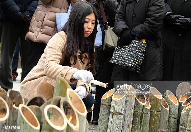 A woman lights bamboo candle that are placed in the shape of the date 311 to commemorate victims of Great East Japan Earthquake and Tsunami in front...
