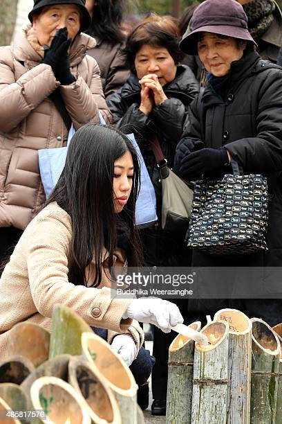 A woman lights bamboo candles placed in the shape of the date 311 to commemorate the victims of Great East Japan Earthquake and Tsunami in front of...