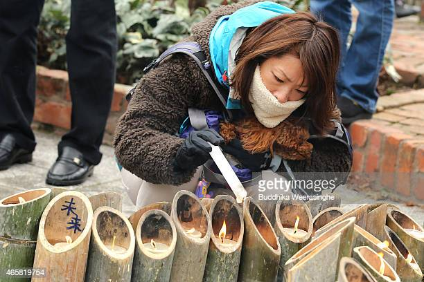A woman lights bamboo candles that are placed in the shape of the date 311 to commemorate the victims of Great East Japan Earthquake and Tsunami in...