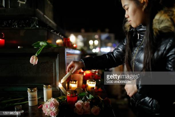 A woman lights candles at a makeshift memorial in Hanau near Frankfurt am Main western Germany on February 20 after at least nine people were killed...