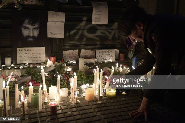 A woman lights candles at the door of the judicial morgue where an autopsy of the corpse of Santiago Maldonado disappeared on August 1st during a...