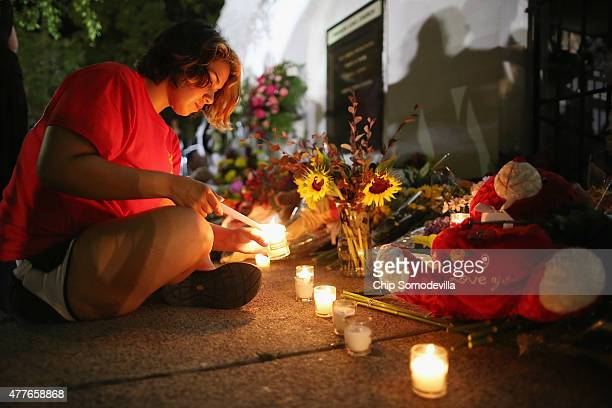 A woman lights candles for the nine victims of last night's shooting at the historic Emanuel African Methodist Episcopal Church June 18 2015 in...