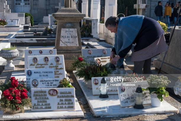 A woman lights candles in one of the tombs at the old cemetery behind the Parish Church of Matosinhos during the visit by participants of Gastronomic...