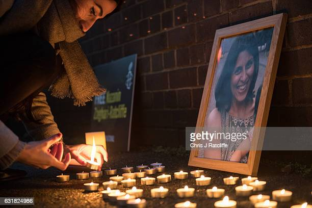Woman lights candles marking the number of days Nazanin Zaghari-Ratcliffe has been imprisoned for next to a photo of her during a vigil for...