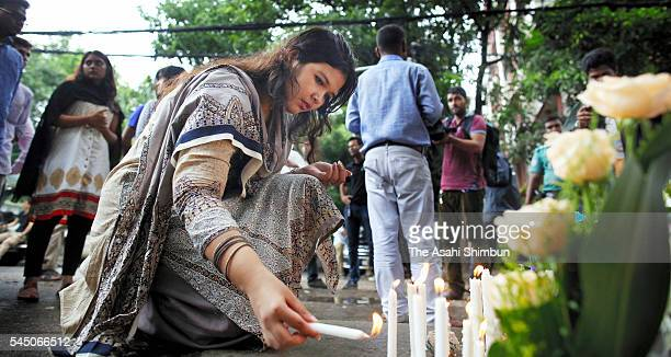 A woman lights candles near the terror attack site on July 5 2016 in Dhaka Bangladesh 20 people including 7 Japanese were killed at the terror attack...