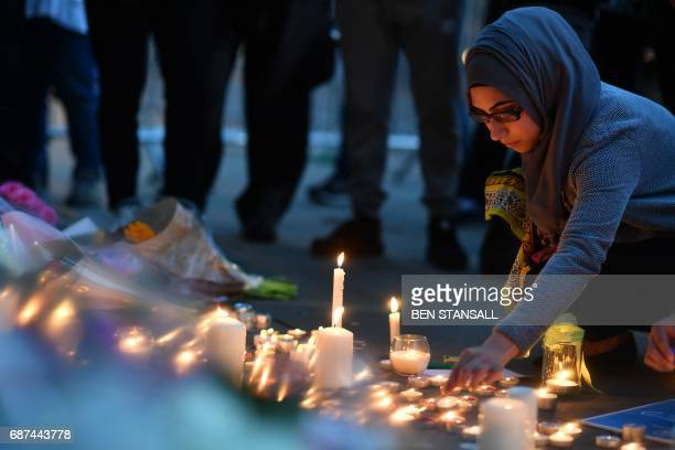 TOPSHOT A woman lights candles set up in front of floral tributes in Albert Square in Manchester northwest England on May 23 in solidarity with those...