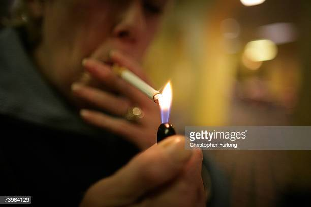 A woman lights her cigarette as she plays bingo at Carlton Bingo Hall in Orrell Park Liverpool on April 24 2007 in Liverpool England Liverpool will...