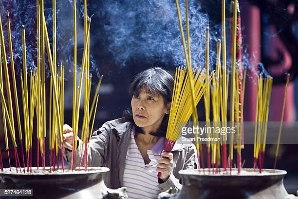 A woman lights incense at the Thien Hau Pagoda Ho Chi Minh City Vietnam