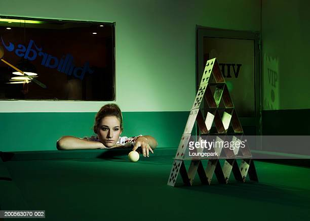 Woman lining up pool ball in front of house of cards