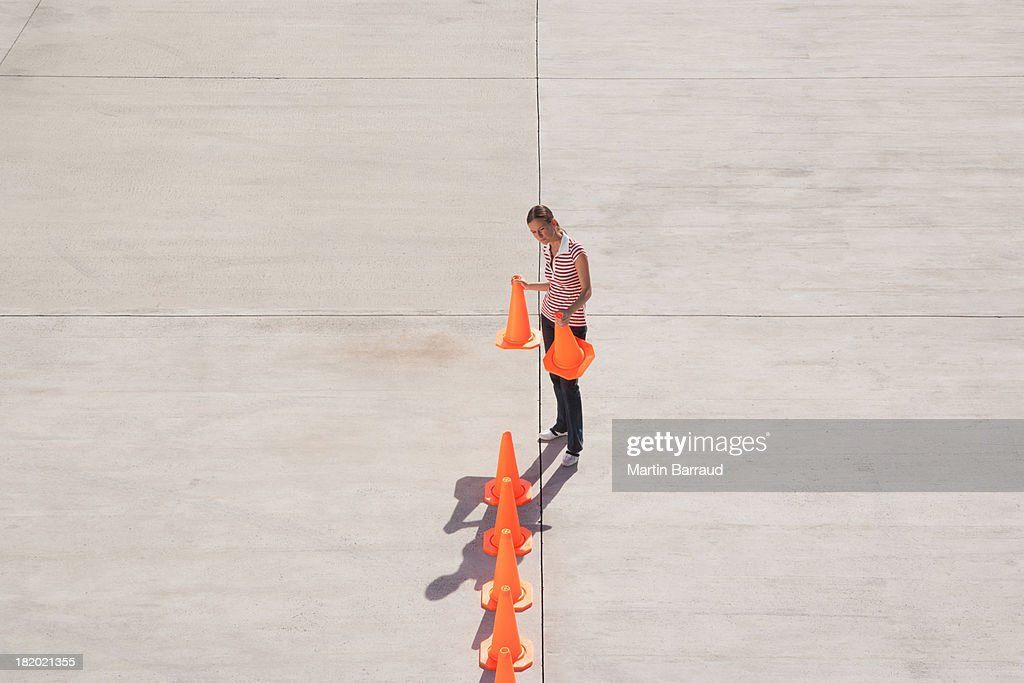 Woman lining up traffic cones : Stock Photo