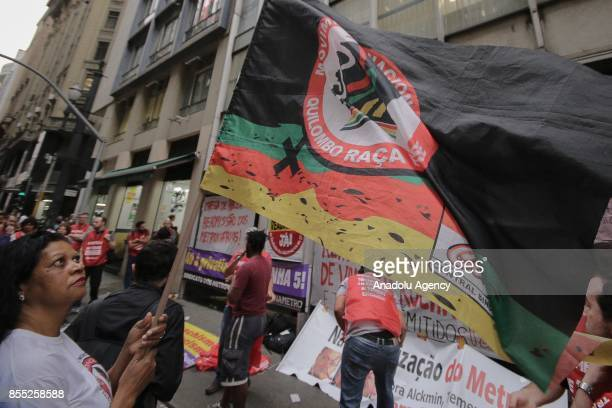 A woman linked to the Subway Workers' union holds a flag during a demonstration against employee layoffs and the expansion of the privatization of...