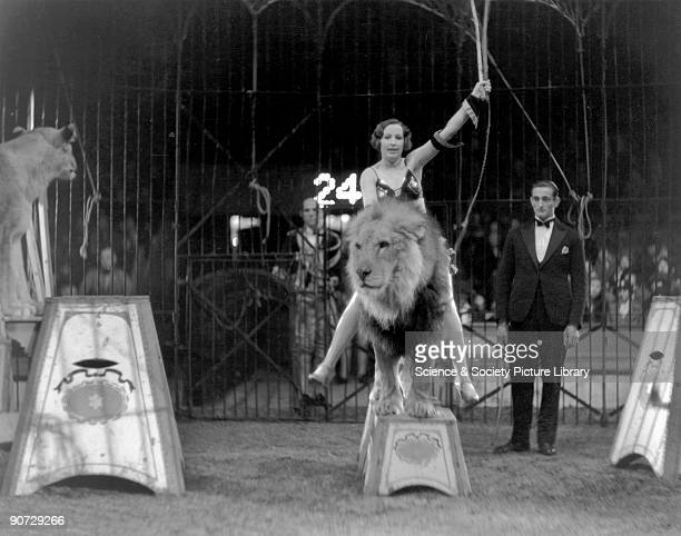 Woman lion tamer sitting on the back of a lion during a circus performance c 1920s