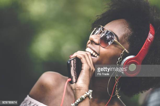 woman listening music at park - music stock pictures, royalty-free photos & images