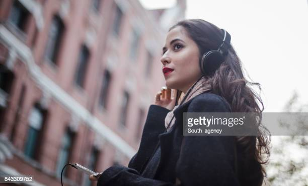 woman listening music downtown - long purse stock photos and pictures