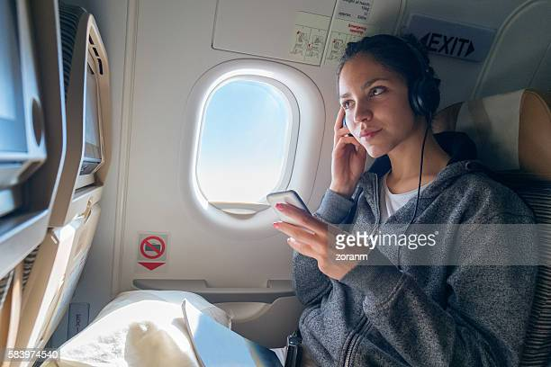 Woman listening music in airplane