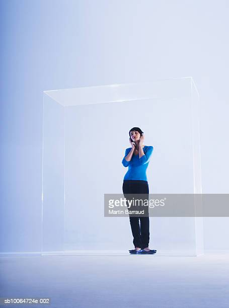 Woman listening music in glass cabinet