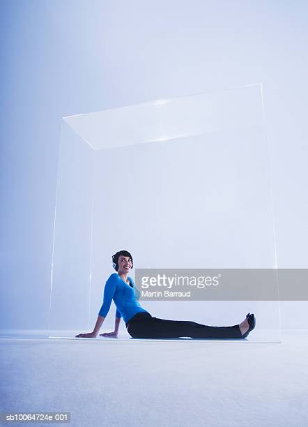 Woman listening music in glass cabinet, smiling
