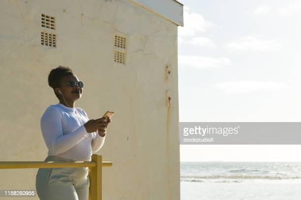 woman listening music on mobile phone at beach - província do cabo ocidental imagens e fotografias de stock