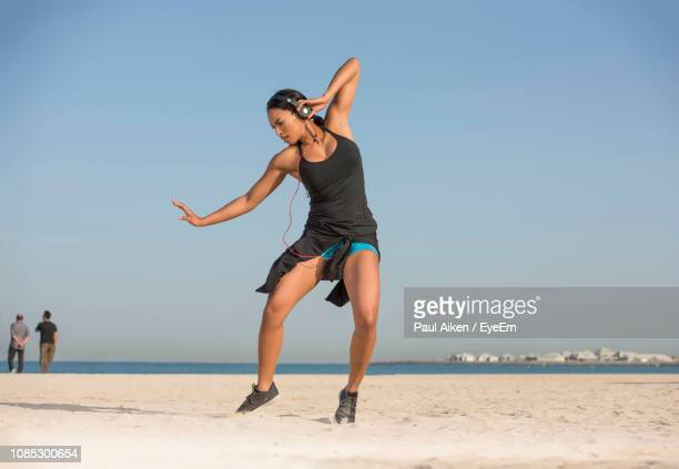 woman listening music while dancing at beach against clear sky - weekend activities stock pictures, royalty-free photos & images