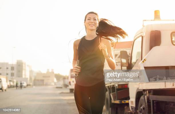 woman listening music while running on road - aikāne stock pictures, royalty-free photos & images