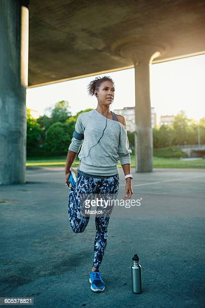 Woman listening music while stretching and standing on one leg