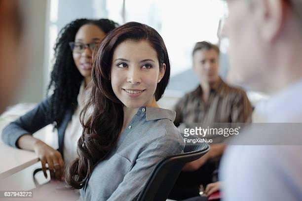 woman listening to business colleague talk during meeting - selective focus stockfoto's en -beelden